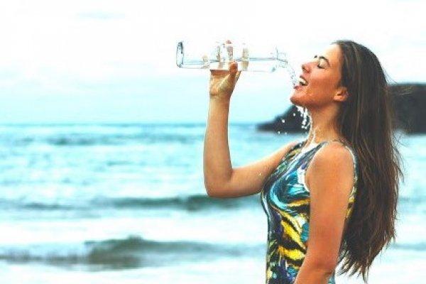 women-by-the-sea-in-bathing-suit-drinking-bottled-wateraa